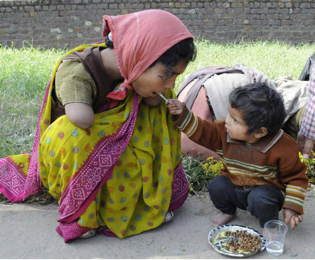 2 years old offering food to her handicapped mother