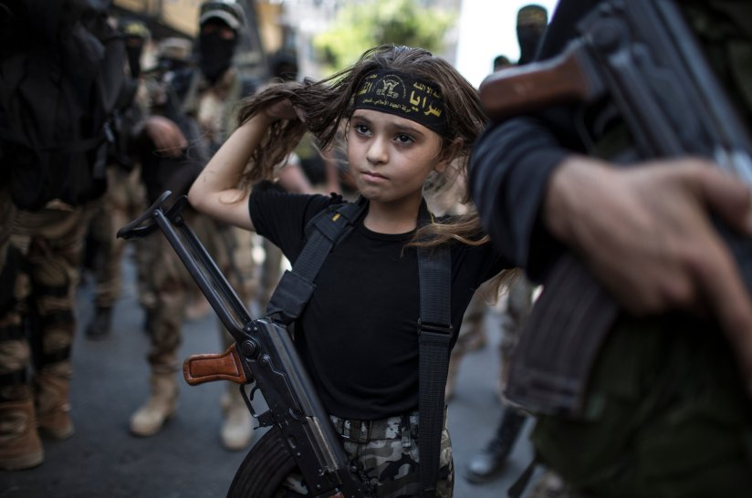 a Palestinian girl with a Kalashnikov rifle, amid militans in Gaza City
